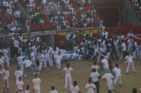 Runners form a bridge for the bull to jump over, into the ring